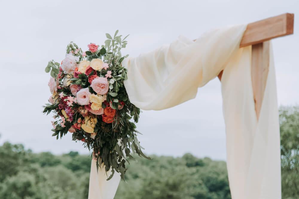 Foto de flores colgando de un arco adornado para una boda
