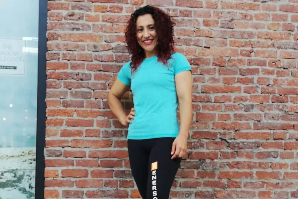 Foto de persona parada frente a un muro sonriendo