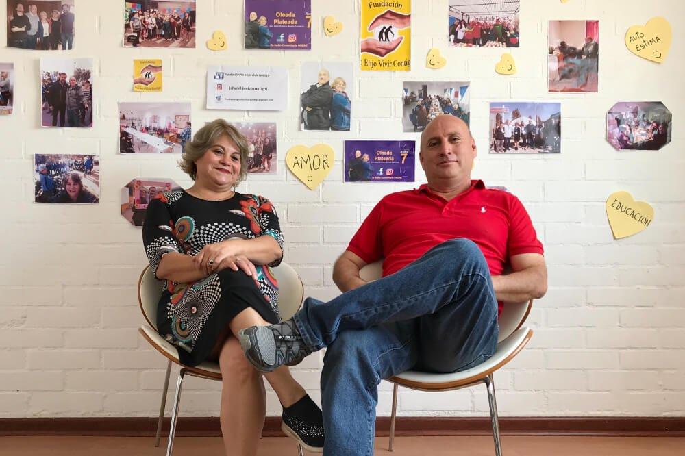 Foto de personas sentadas en una silla, con fotos a sus espaldas de gente sonriendo