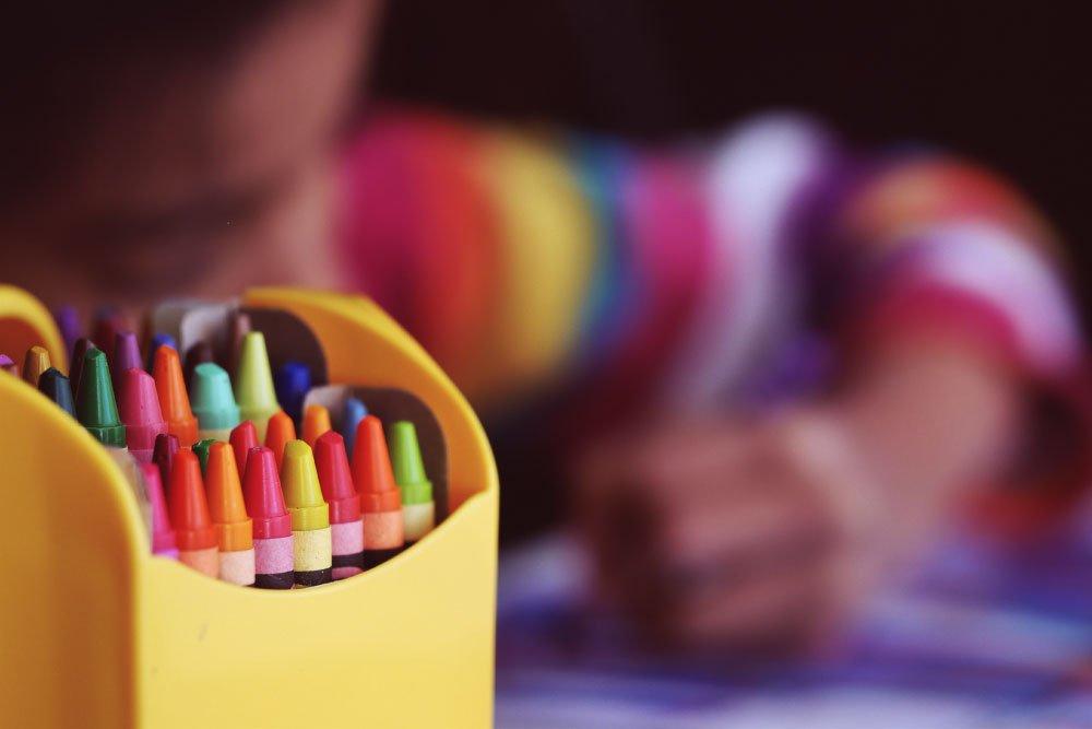 Foto de niño pintando con lapices de colores