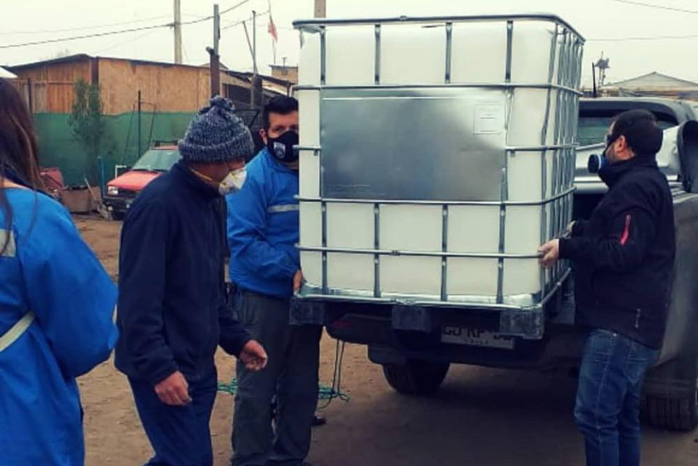Foto de personas realizando entrega de amonio cuaternario en asentamiento millantun de puente alto