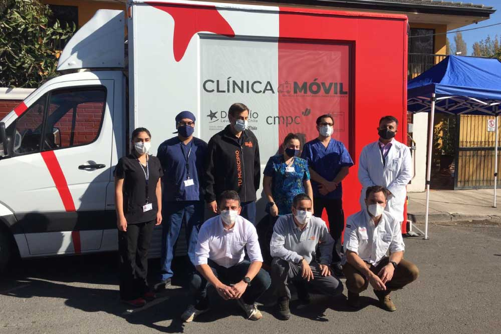 Foto de personas sentadas al costado de un furgón clinico de color rojo con blanco en puente alto