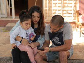 Foto de una familia, dos personas adultas y una niña de 4 años